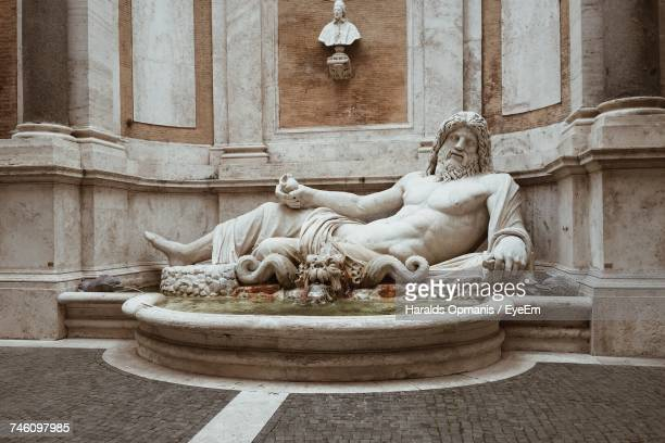 statue by wall - greek god stock pictures, royalty-free photos & images