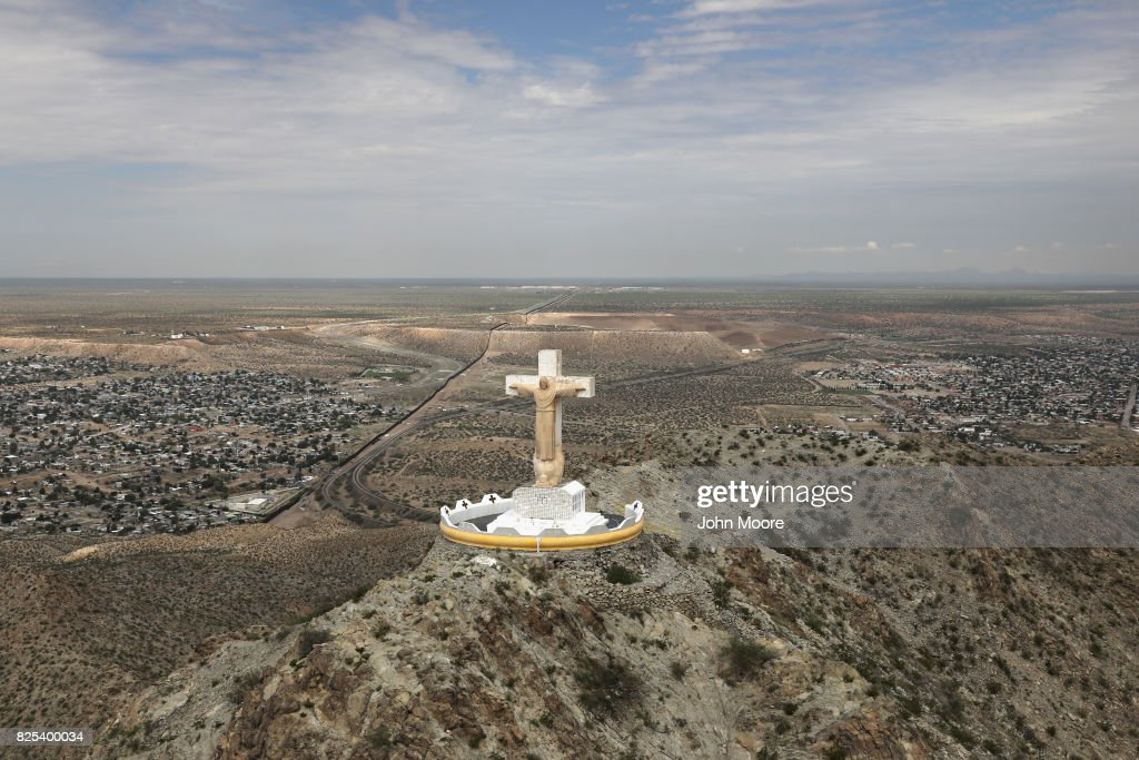 A statue Christ of the Rockies overlooks the U.S.-Mexico border on August 1, 2017 as seen from a U.S. Customs and Border Protection helicopter near Sunland Park, New Mexico. Logistical challenges, such as rugged terrain, are just some of the complications facing the construction of a border wall proposed by President Trump.
