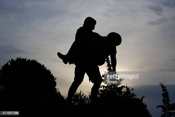 Statue depicting a Turkish soldier carrying an injured Anzac soldier in the bloody Gallipoli campaign in the World War I is silhouetted in Gallipoli...