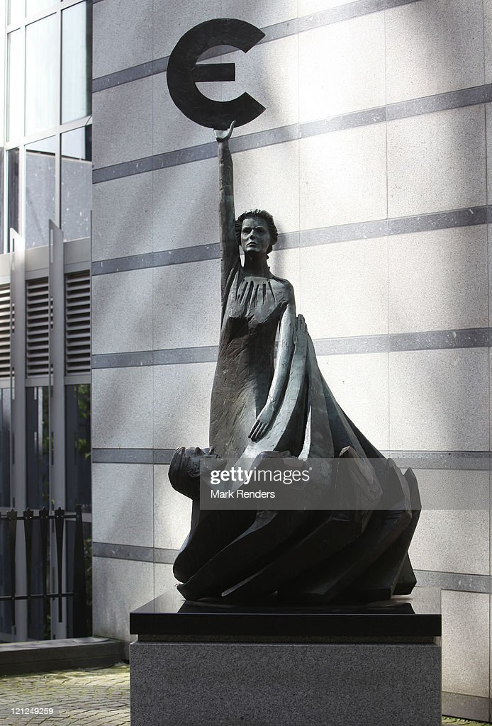 A statue holding the symbol of the Euro, the European common currency, stands in front of the European Parliament building on August 16 and 2011 in Brussels, Belgium. The German Chancellor Angela Merkel met with the French President Nicolas Sarkozy in Paris today to discuss the European debt crisis. The two leaders of the eurozone's major economies have urged members to coordinate through an economic government that will consist of the 17 heads of the eurozone states.