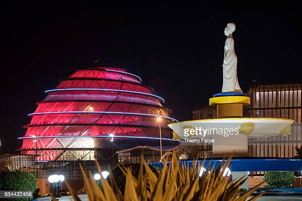 A statue honouring the strength of Rwandese women and the construction site of the Kigali Convention Centre are illuminated at night Kigali with a...