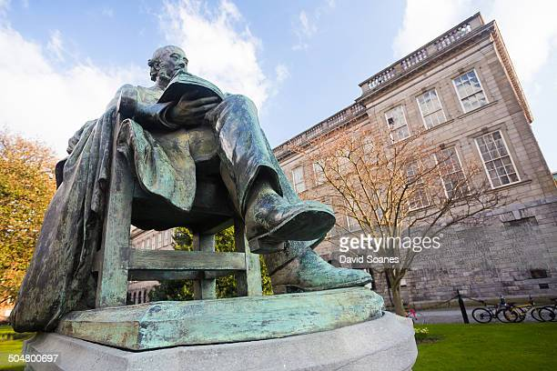 Statue in Trinity College with the exterior of the Old Library in the background.