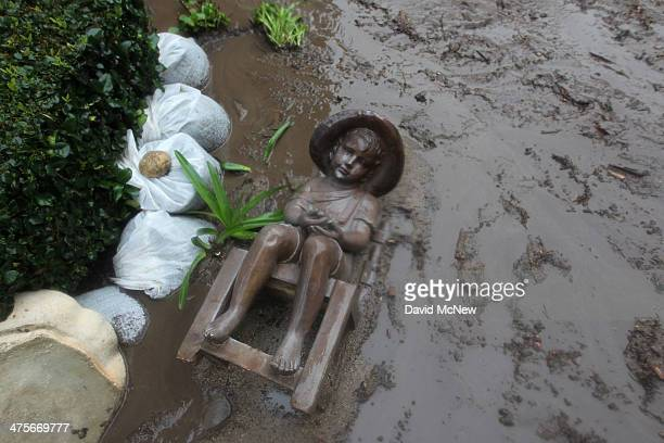 A statue lies in ash water and mud in a backyard below the Colby Fire burn area as a storm brings rain in the midst of record drought on February 28...