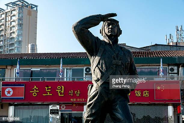 A statue of a Chinese air force soldier in Korea war stands beside the Yalu River looking out to the direction of North Korea Dandong is the largest...