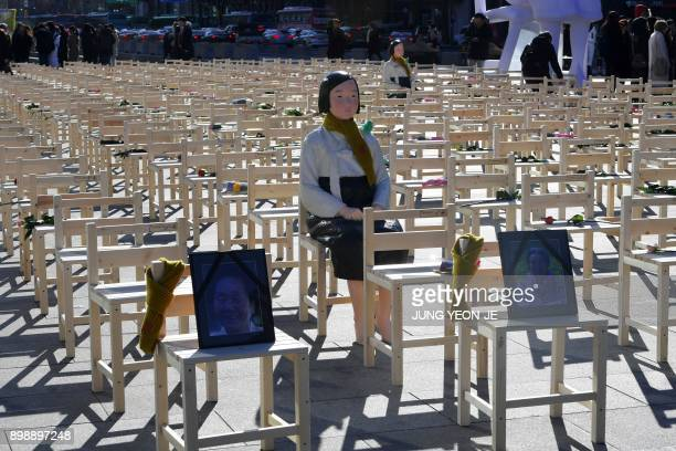 A statue of a comfort woman is displayed in an installation of empty chairs set up in central Seoul to commemorate the death of eight former sex...