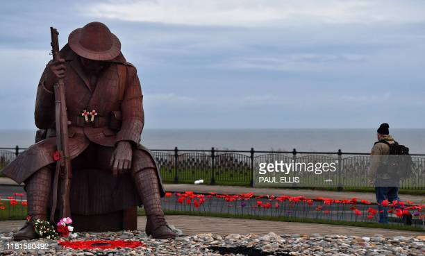A statue of a First World War soldier known locally as Tommy is seen at first light at Seaham north east England on November 11