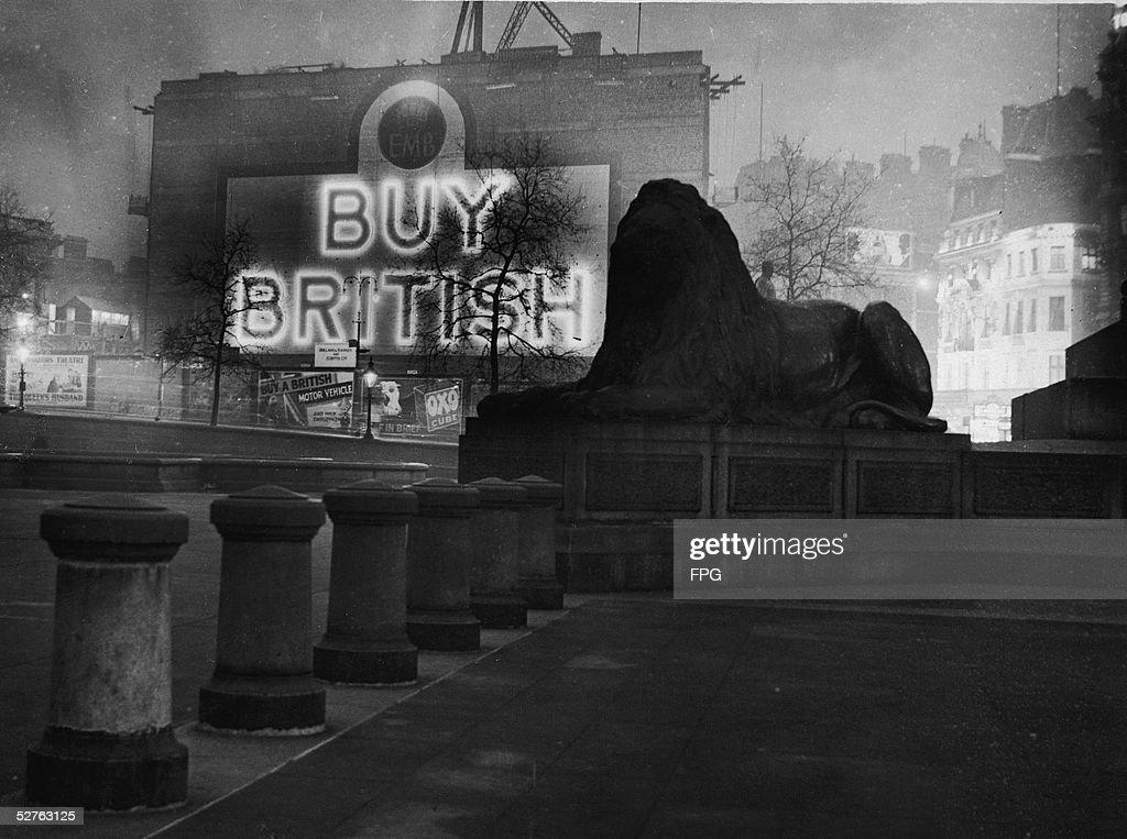 A statue of a lion in Trafalgar Square is silhoutted against a giant illuminated sign which reads 'Buy British' and which is part of a campaign to encourage the consumption of British-made goods, London, November 16, 1931.