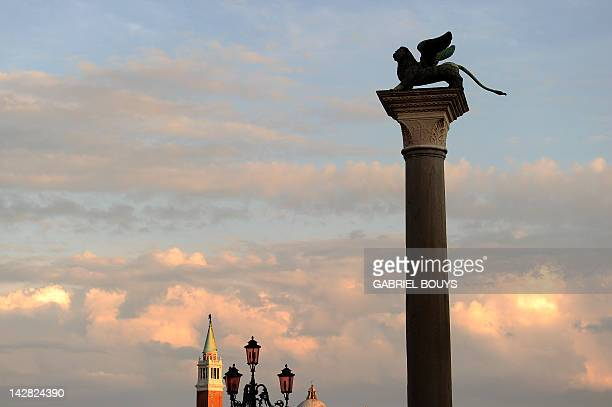 A statue of a lion sits on top of a column in the Piazzetta on Piazza San Marco on April 12 2012 in Venice AFP PHOTO / GABRIEL BOUYS