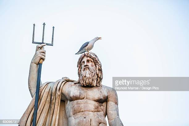 statue of a male figure with beard and pitchfork and a bird perched on its head, fountain of neptune, peoples square - neptune roman god stock pictures, royalty-free photos & images