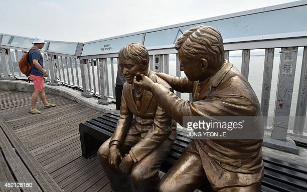 A statue of a man comforting a person is placed to dissuade suicides on Mapo Bridge a common site for suicides over the Han river in Seoul on July 14...