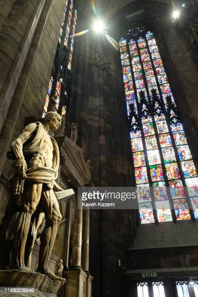 A statue of a man highlighting his body anatomy stands erect in front of high coloured windows inside Milan Cathedral also known as Duomo di Milano...