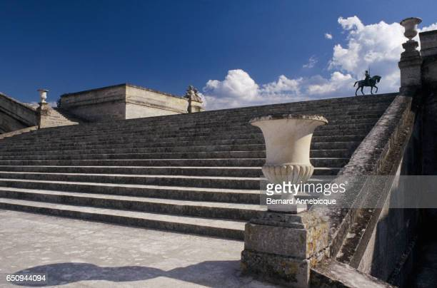 A statue of a man riding a horse on the stairway at the Chantilly Estate