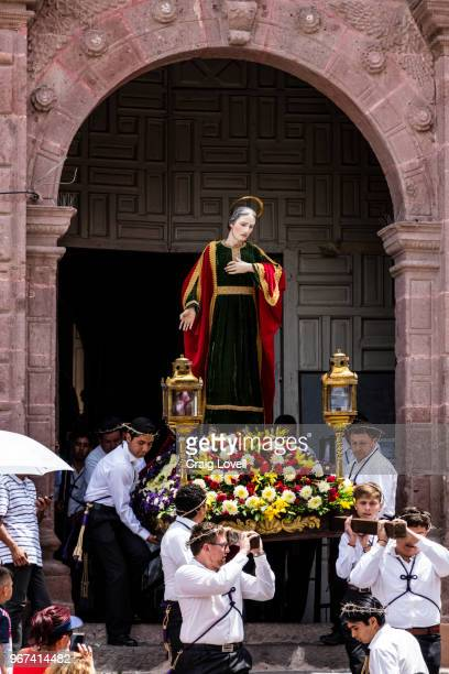A statue of a saint is carried down the steps of the SAN RAFAEL chapel during the Good Friday Procession called Santo Encuentro - SAN MIGUEL DE ALLENDE, MEXICO