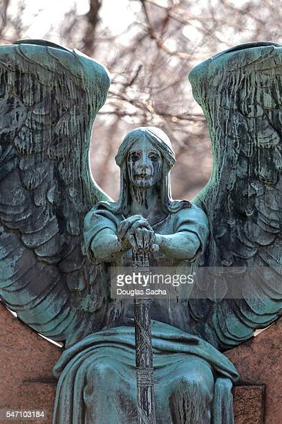 statue of a sitting angel - angel of death foto e immagini stock