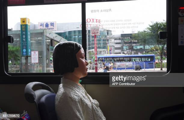 A statue of a teenage girl symbolizing former comfort women who served as sex slaves for Japanese soldiers during World War II is pictured on a bus...