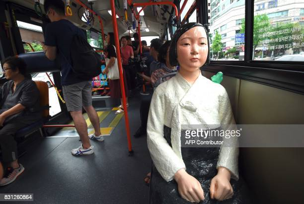 A statue of a teenage girl symbolizing former comfort women who served as sex slaves for Japanese soldiers during World War II is mounted in a bus...