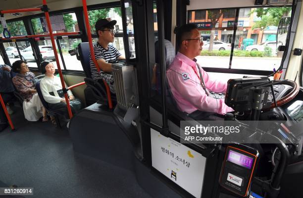 """Statue of a teenage girl symbolizing former """"comfort women"""" who served as sex slaves for Japanese soldiers during World War II, is pictured on a bus..."""