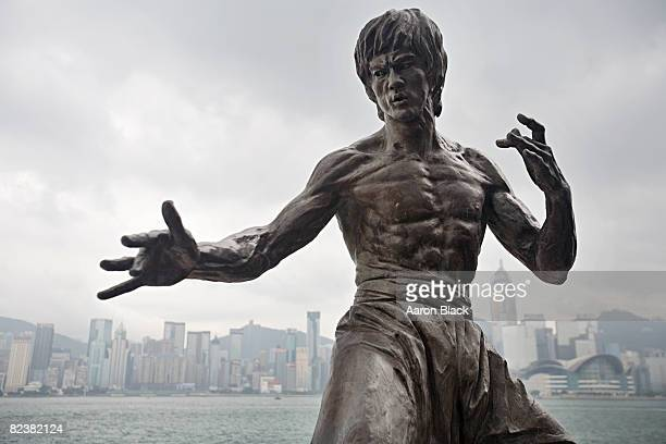 Statue of a very muscular looking Bruce Lee posing in a martial art stance.