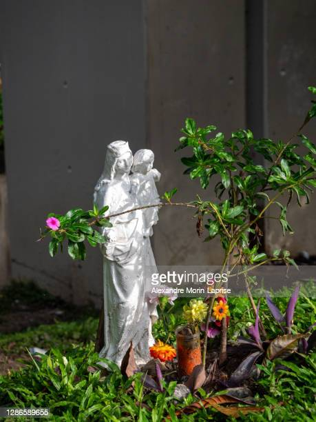 statue of a virgin holding the baby jesus surrounded by flowers and leaves - sculpture stock pictures, royalty-free photos & images