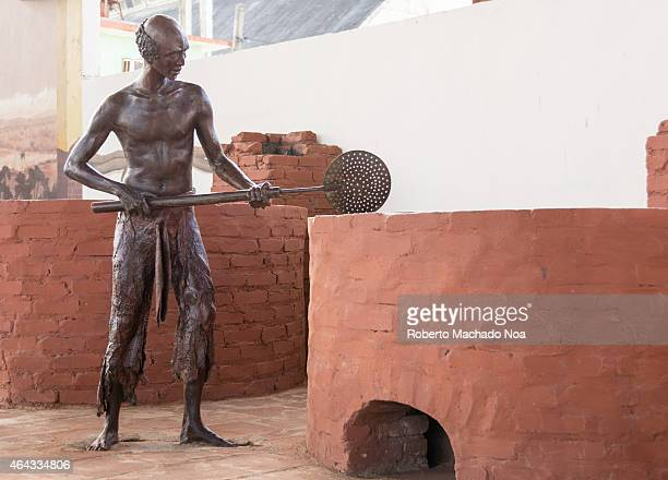Statue of African slave working in a vintage Cuban sugar mill conserved as a tourist attraction the place shows a historic timeline of the sugar...