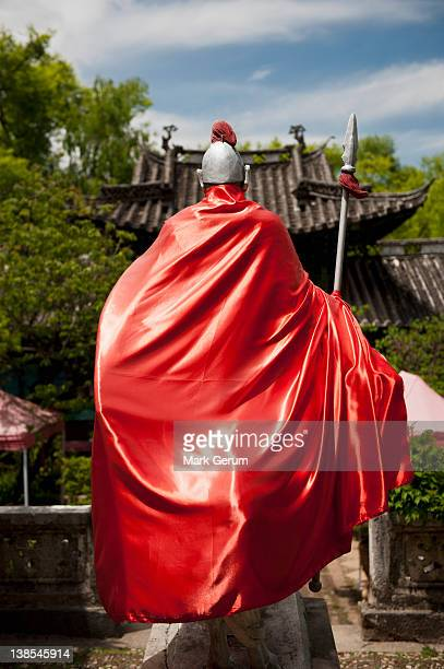 statue of ancient chinese warrior in lijiang, china - cape garment stock photos and pictures
