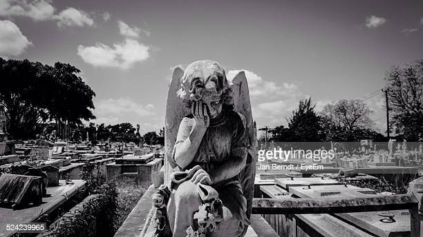 statue of angel crying in cemetery - angel of death foto e immagini stock