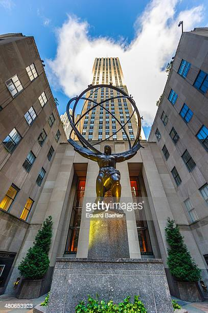CONTENT] Statue of Atlas with Rockefeller Tower from low perspective agaisnt cloudy sky in Manhattan