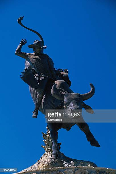 statue of bucking bull with cowboy in wyoming - bucking stock photos and pictures