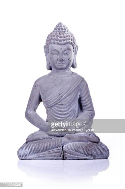 statue of buddha against white background - buddha foto e immagini stock