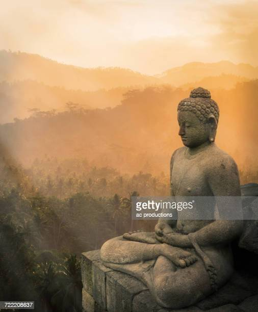 statue of buddha at sunset, borobudur, java, indonesia - buddha foto e immagini stock