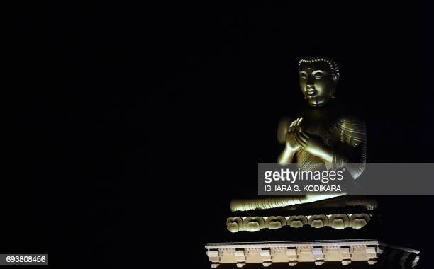 A statue of Buddha is diplayed in a temple in the Colombo suburb of Kelaniya on June 8 during the Poson Festival marking the introduction of Buddhism...