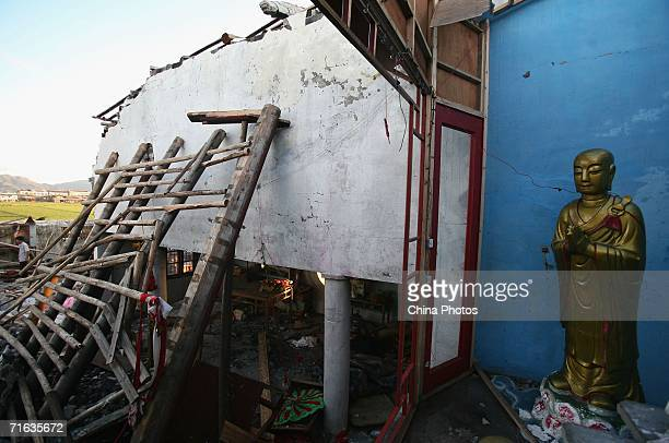 A statue of Buddha is seen at a collapsed temple after typhoon Saomai landed at Dongdianbao Village on August 12 2006 in Cangnan County of Zhejiang...