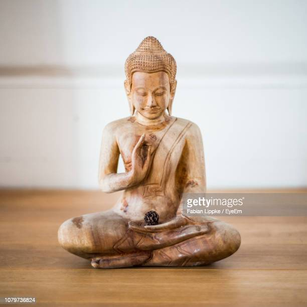 statue of buddha on table - buddha stock pictures, royalty-free photos & images