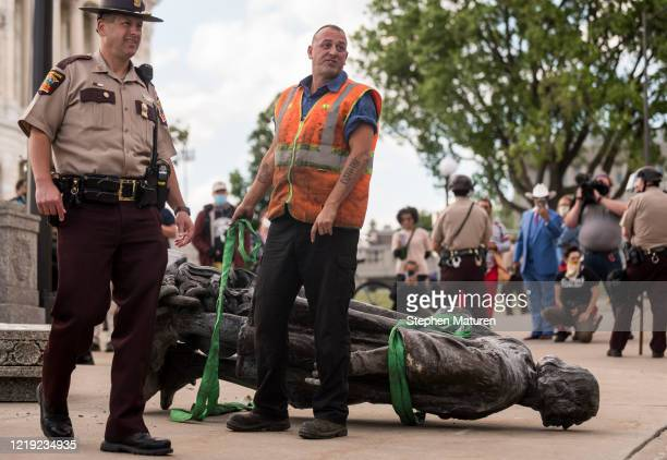 A statue of Christopher Columbus which was toppled to the ground by protesters is loaded onto a truck on the grounds of the State Capitol on June 10...