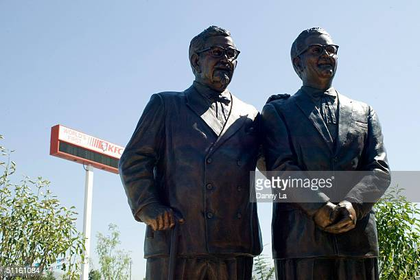 A statue of Colonel Harland Sanders and Pete Harman stands at the newly rebuilt first KFC location on August 11 2004 in Salt Lake City Utah The...