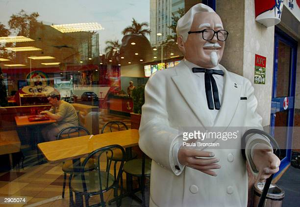 A statue of Colonel Harland Sanders founder of Kentucky Fried Chicken stands on the street one of the fast food restaurants in Bangkok Thailand...