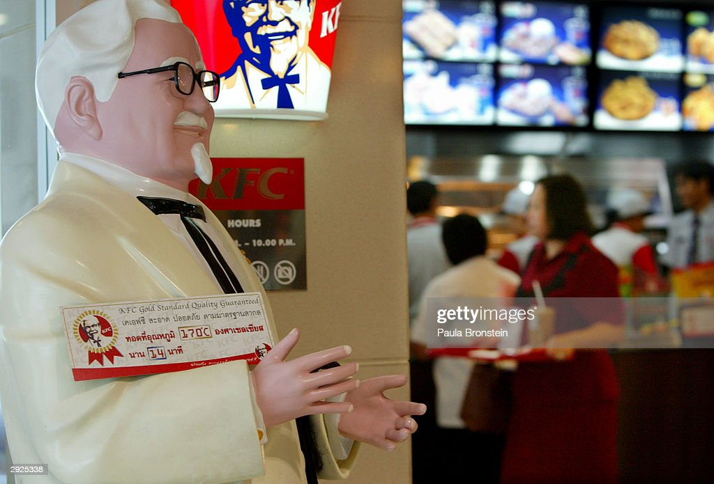 A statue of Colonel Sanders, founder of Kentucky Fried Chicken (KFC), stands outside one of the fast food restaurants with a sign displayed guaranteeing quality control February 3, 2004 in Bangkok, Thailand. An outbreak of bird flu has ravaged poultry farms and could devastate the country's chicken export sector, worth 1.5 billion dollars, which is the fourth largest in the world. Although the Thai government is trying to calm its people about the deadly virus, fear of eating chicken has affected restaurants, with business remaining slow.