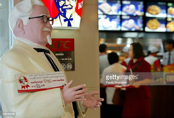 A statue of Colonel Sanders founder of Kentucky Fried Chicken stands outside one of the fast food restaurants with a sign displayed guaranteeing...