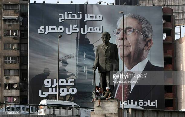 A statue of Egyptian novelist Naguib Mahfouz is seen in front of a huge election campaign banner for former foreign minister and Arab League chief...