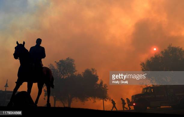 A statue of former US President Ronald Reagan titled Along The Trail stands outside the Reagan Presidential Library as the Easy Fire burns on October...