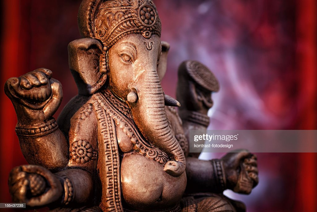 A statue of Ganesha, a deity of India on red background : Stock Photo