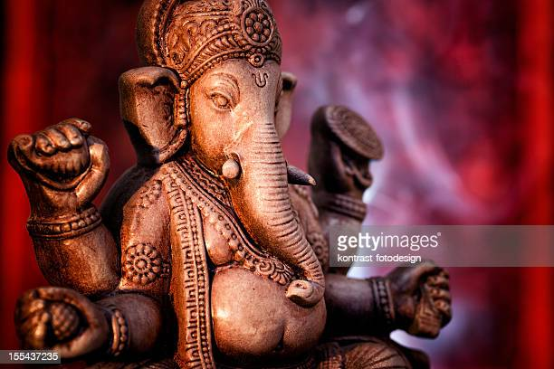 A statue of Ganesha, a deity of India on red background