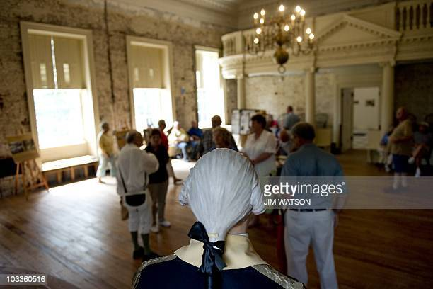A statue of General George Washington stands as a tour guide dressed in colonial costume shows leads a tour of the State House in Annapolis MD August...