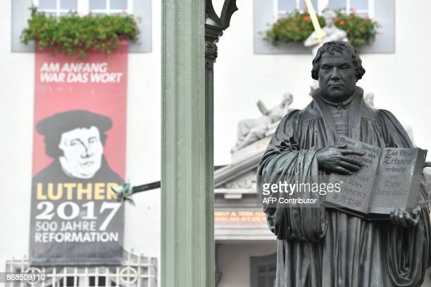A statue of German Church reformer Martin Luther holding a book including his translation into German of the New Testament of the Bible is pictured...