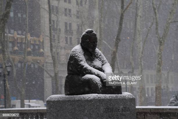 A statue of Gertrude Stein in the snow in Bryant Park in New York March 21 2018 as the fourth nor'easter in a month hits the tristate area on the...