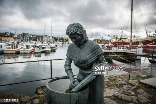 Statue of girl cleaning a fish is seen next to the harbour on September 05, 2018 in Torshavn, The Faroe Islands. The Faroe Islands, situated between...