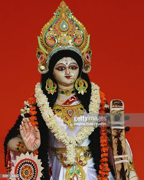 statue of goddess saraswati against red background - saraswati stock photos and pictures
