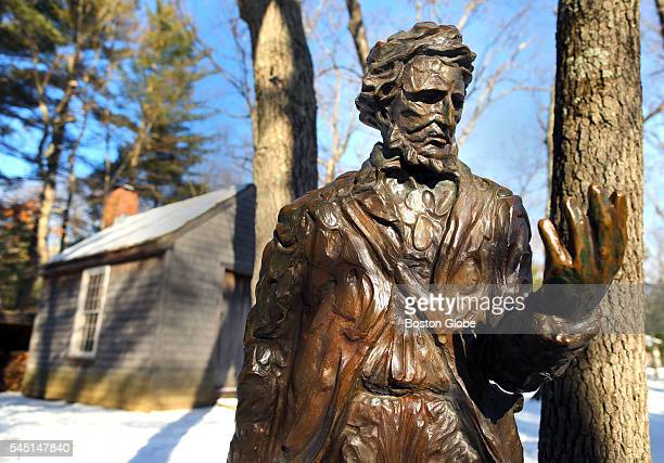 A statue of Henry David Thoreau in front of a reproduction of his cabin at the Walden Pond Reservation in Concord Mass on Jan 20 2016