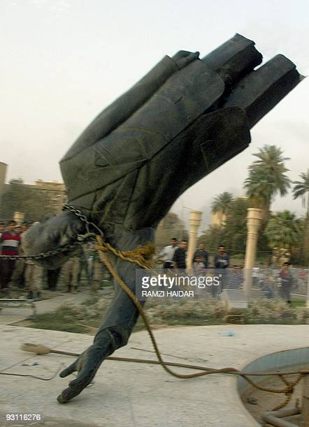 A statue of Iraqi President Saddam Hussein falls after it was pulled down by a US Marine vehicle in Baghdad's alFardous square 09 April 2003 Iraqis...