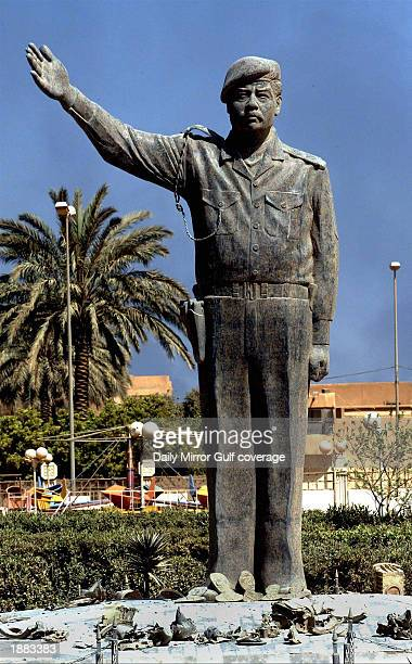 A statue of Iraqi President Saddam Hussein remains near the AlMahmoon telephone exchange and telecommunication center destroyed overnight March 28...